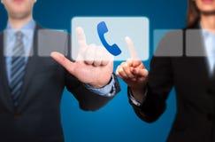 按电话按钮和滴答作响的商人和女实业家 库存图片
