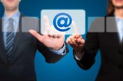 按联络的商人和女实业家给按钮发电子邮件和 免版税库存图片
