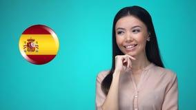 按西班牙旗子按钮的快乐的女性,准备好学会外国语 影视素材