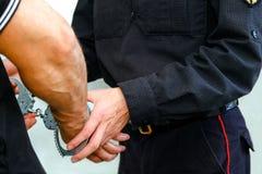按钮逮捕手铐一名被拘捕的罪犯 警察局的人 在被扣留的人的腕子的手铐 免版税图库摄影