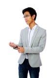 按他的夹克的英俊的亚裔人 库存图片