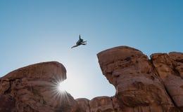挑战、风险和自由概念 现出轮廓跳过悬崖横穿峭壁的一个人 免版税库存照片