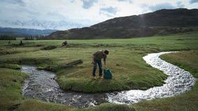 挑运的徒步旅行者人走向山小河把一些水引入烧瓶 影视素材