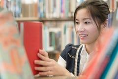 挑选一本红色书的女孩 免版税库存照片