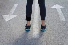 挑选概念 站立在箭头之间的妇女显示不同的方向 前进或回去,向前 免版税库存照片