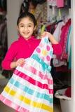 挑选从壁橱的小女孩一件礼服 免版税库存图片