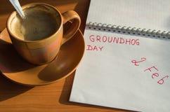 挖土日与2月2日日期和杯的2月笔记薄浓咖啡 免版税库存图片