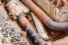 挖掘坑 有不锈的修理的袖子成员的老饮料水管 完成被修理的管道系统等待 库存照片