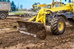 挖掘机、运转在地面的倾销者卡车和推土机在建造场所 图库摄影