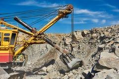 挖掘机与花岗岩或矿石一起使用在露天矿 图库摄影