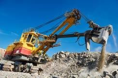 挖掘机与花岗岩或矿石一起使用在露天矿 免版税库存图片