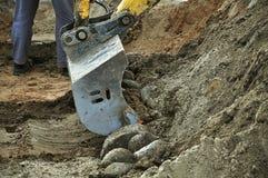 挖掘机倾吐石头 库存照片