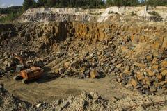 挖掘机和玄武岩专栏岩石 重工业 石挖掘 生产石头由玄武岩柱子 免版税图库摄影