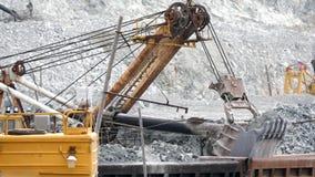挖掘机和铁路与矿石 挖掘机用矿石有轨机动车在露天开采矿背景中填装  在采矿的重的运输 股票录像