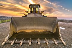 挖掘机在一个工作日结束时在建造场所 免版税库存图片
