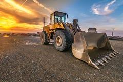 挖掘机在一个工作日结束时在建造场所 库存图片
