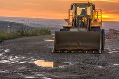 挖掘机在一个工作日结束时在建造场所 免版税库存照片