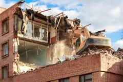 挖掘机在一个明亮的晴天毁坏并且破坏大厦 免版税库存图片