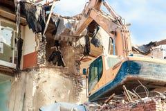 挖掘机在一个明亮的晴天毁坏并且破坏大厦 库存照片