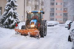 挖掘机在城市清洗雪街道  免版税库存照片
