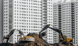 挖掘机在多楼层房子背景的地面上运转  免版税库存照片
