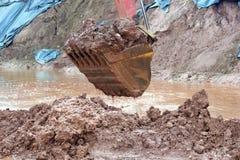 挖掘机在大量掘土的过程中取消泥 图库摄影