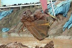 挖掘机在大量掘土的过程中取消泥 免版税库存图片
