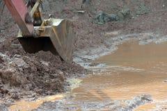 挖掘机在大量掘土的过程中取消泥 免版税库存照片