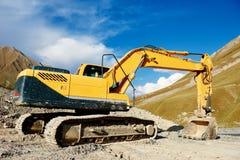 挖掘机在山修路站点的装载者机器 免版税库存图片