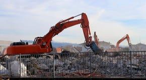 挖掘机在工作,在瓦砾和尘土之间,城市再开发的 免版税图库摄影