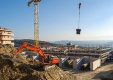 挖掘机在建造场所汇编加工与增强滤网的一个巨大的模子concreting的 免版税库存照片
