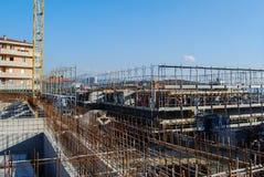 挖掘机在建造场所汇编加工与增强滤网的一个巨大的模子concreting的 免版税库存图片