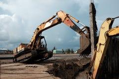 挖掘机在海滩的修造防堤 库存图片