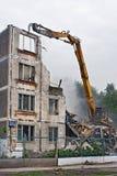 挖掘机在莫斯科毁坏老苏联住宅房子 库存照片