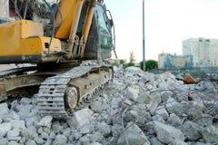 挖掘机在被毁坏的混凝土站立 在工地工作的挖掘机毛虫 在石头的建筑器材和 库存照片