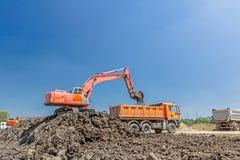挖掘机在建筑工地装载一辆卡车 免版税库存图片