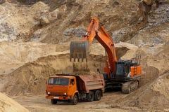 挖掘机工作在他的事业的 免版税库存照片