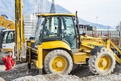 挖掘机开掘坑,工作者指挥工作 库存图片