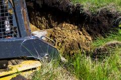 挖掘机开掘的基础坑播种的看法在象草的领域的在乡下 图库摄影