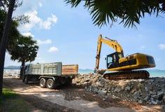 挖掘机挖掘机的石头和运转在海滩海海洋的工地工作/反向铲装载者的翻斗车 库存照片