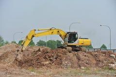 挖掘机机器用于在建造场所挖掘土壤 免版税库存图片