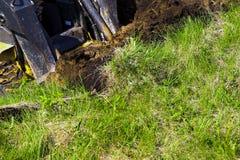 挖掘机桶开掘的坑部份看法在象草的土壤的在地球工作期间 免版税库存图片