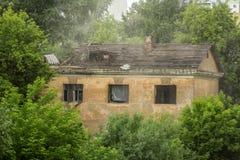挖掘机桶打破在绿色树中的老房子 免版税图库摄影