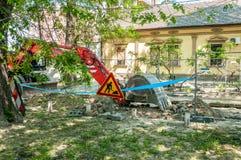 挖掘机械挖掘从街道的地面在新的分区供暖管子线的树荫下 库存照片