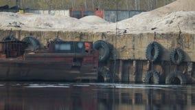 挖掘机水槽的劫掠桶到口岸的河里以老为背景,生锈,葡萄酒驳船 股票录像