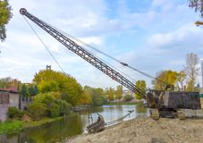 挖掘机清除底部从土和残骸的湖 库存照片