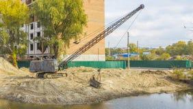 挖掘机清除底部从土和残骸的湖 免版税库存照片
