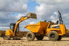 挖掘机的打翻的土壤到站点倾销者卡车里 免版税库存照片