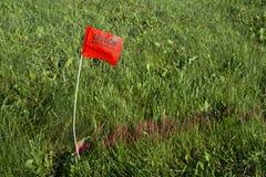 挖掘机的热线旗子被埋没的电能线 免版税库存照片