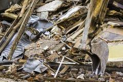 挖掘机老砖瓦房的桶和废墟 免版税图库摄影